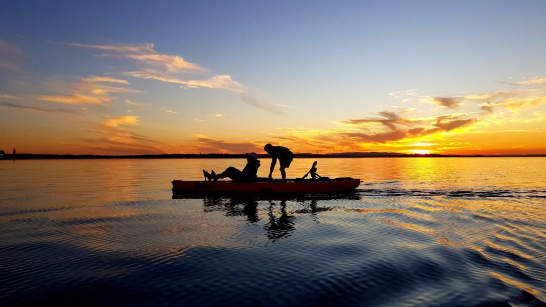 Silhouette Kids on kayak in the sunset,